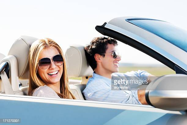 Beautiful couple driving in their Convertible car