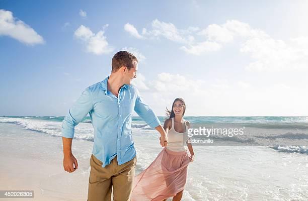 Beau couple tenant les mains et courez à la plage.