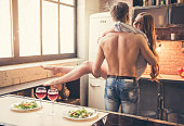 Handsome muscular guy is holding his beautiful girlfriend in arms while they are having a romantic dinner together in the kitchen
