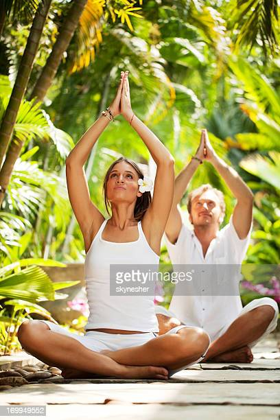 Beautiful couple meditating in a tropical resort.