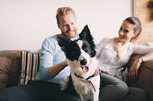 Beautiful couple relaxing at home and loving their pet