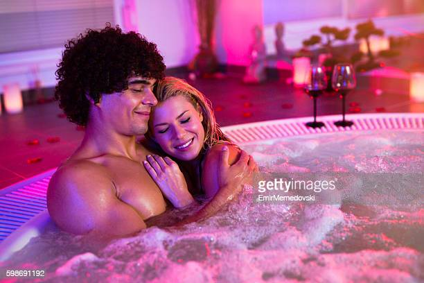 Beautiful couple relaxing in jacuzzi at health spa.