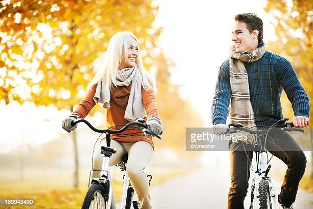 Beautiful couple rides bikes on a  autumn day.