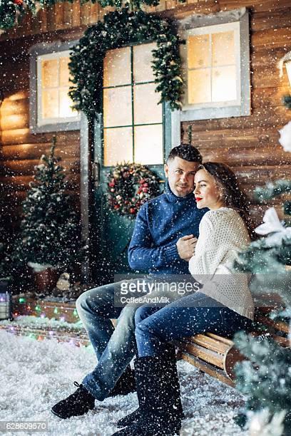 Beautiful couple sitting near their house