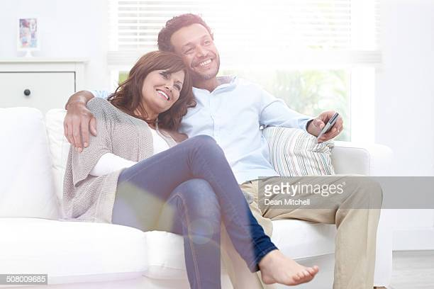 Beautiful couple watching TV at home