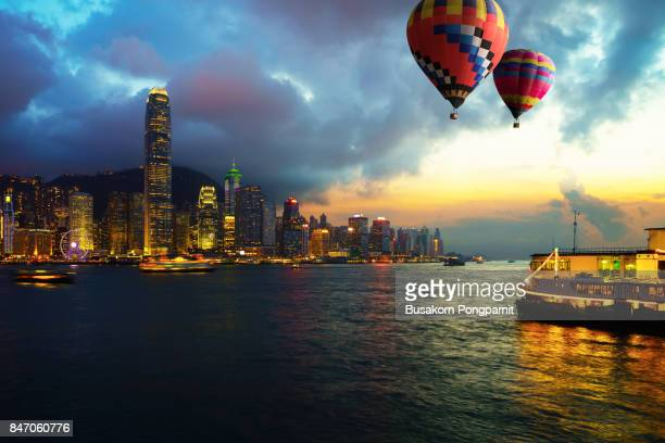 Beautiful Crowded and building in Hong Kong cityscape at sunset, Landscape of Hot air Balloon over Victoria Harbor sky with sunset.