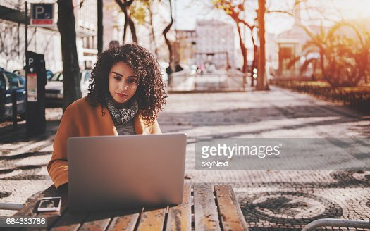 Beautiful curly lady with laptop in street bar : Stock Photo