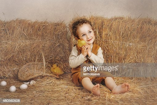 Beautiful curly-haired boy sitting next to a hay duckling ear : Stock Photo