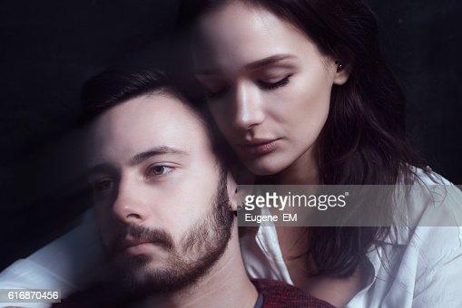 Beautiful cute loving couple in a studio with dark walls : Stock Photo