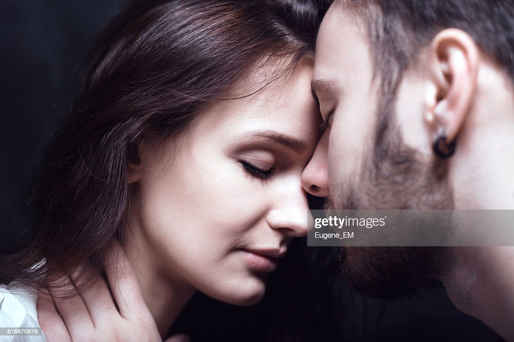 Beautiful cute loving couple in a studio with dark walls : Stock Photo