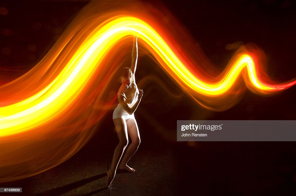 beautiful dancer gracefully under orange stream : Foto stock