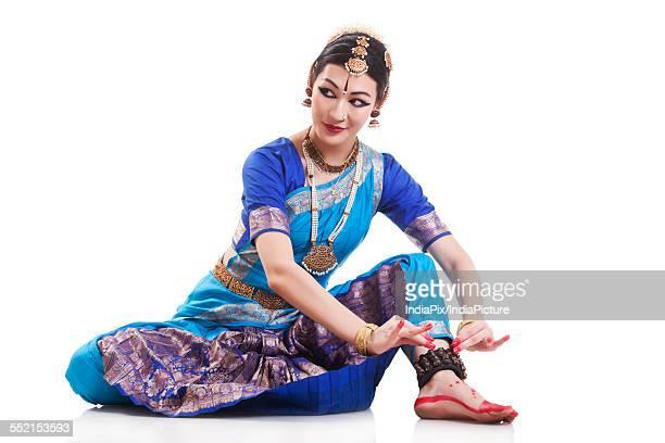 Beautiful dancer performing Bharatanatyam against white background