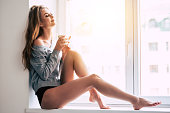 Beautiful young woman holding coffee cup and keeping eyes closed with smile while sitting at windowsill at home