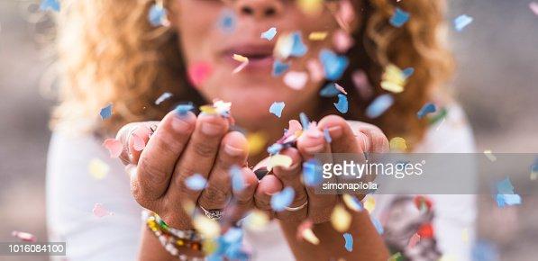 confeti de golpe hermosa mujer defocused de manos. concepto de celebración y evento. felicidad y color de la imagen. movimiento y la felicidad que se divierten : Foto de stock