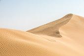 Beautiful simple image of a remote sandy desert landscape of dunes in Liwa desert in Empty Quarter. Abu Dhabi, UAE.