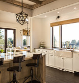 Basking in the warmth of a morning sunrise, this luxury  kitchen features elegant pendant light fixtures, a farmhouse sink, a wood beam ceiling, and a kitchen island. Is fully furnished.