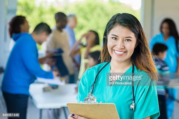 Beautiful doctor smiling at camera holding clipboard