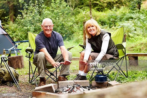 Schönes älteres Ehepaar Schaden zuzufügen Hände am Lagerfeuer
