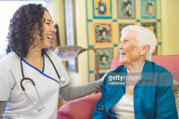 Beautiful elderly woman in apartment interacting with young Hawaiian nurse