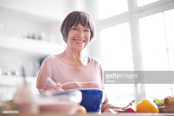Beautiful elderly woman in kitchen smiling