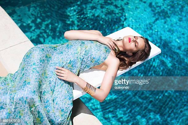 Bela modelo elegante com um bonito vestido postura por piscina
