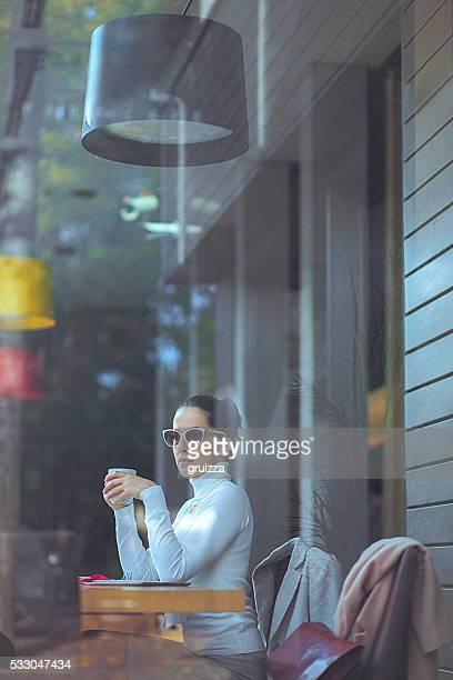 Magnifique, élégant femme appréciant la tasse de café au Café
