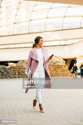Beautiful elegant woman texting on the phone : Stock Photo