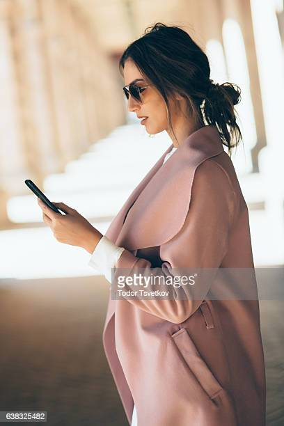 Beautiful elegant woman texting outdoors