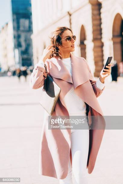 Beautiful elegant woman texting outdoors