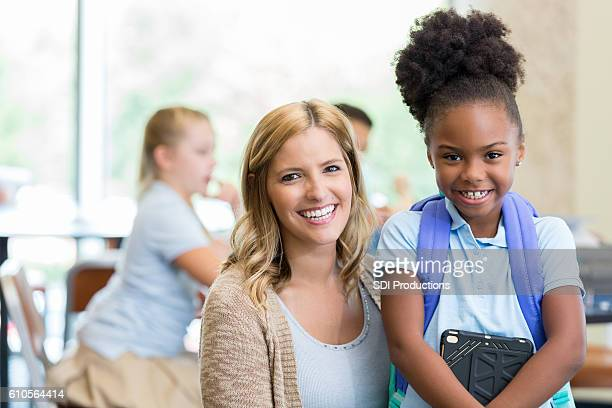 Beautiful elementary school teacher with African American female student