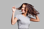 Cute young girl with arms raised dancing and laughing and having fun