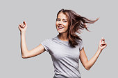 Cute young girl with arms raised dancing and laughing and enjoying life