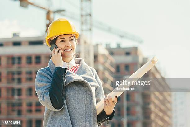 Beautiful engineer at construction site talking on smart phone
