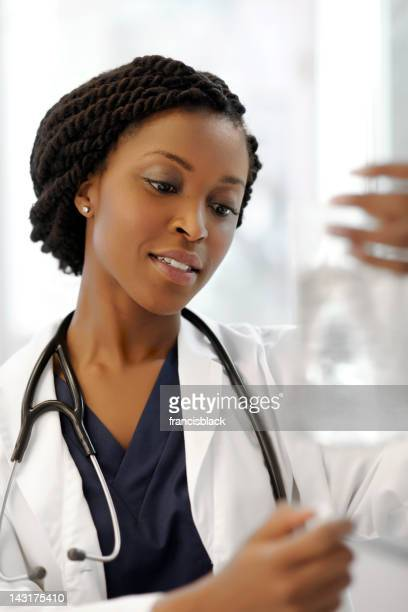 Beautiful ethnic doctor checking intravenous