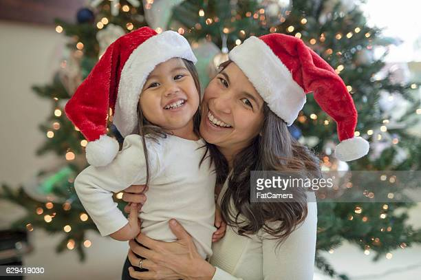 Beautiful ethnic mother and daughter wearing Santa hats for Christmas