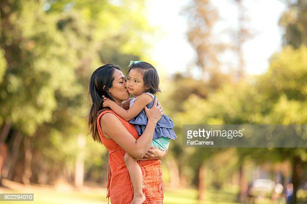 Beautiful ethnic mother kissing her daughter