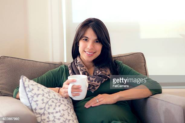 Beautiful ethnic pregnant mother drinking tea and holding belly