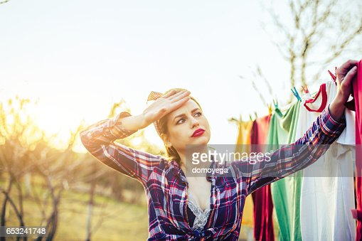 Beautiful exhausted lady hanging a laundry : Stock Photo