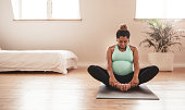 Portrait of young pregnant female working out at home. African pregnant woman practicing yoga at home. Prenatal groins stretch. Buddha Konasana Pose. Pregnancy yoga and fitness.