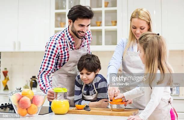 Schöne Familie vorbereiten orange juice in kitchen