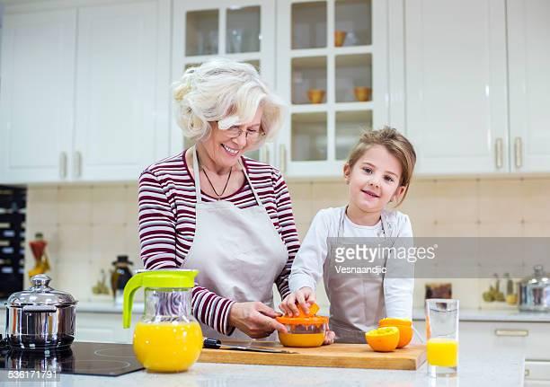 Hermosa familia en la cocina preparando jugo de naranja