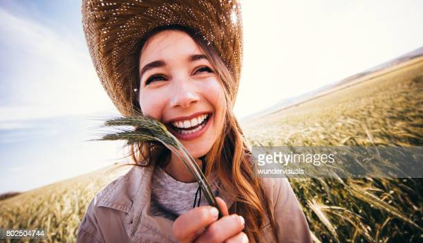 Beautiful farmer girl holding wheat grains and laughing
