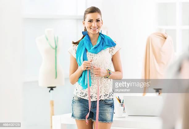 designer de moda bonita segurando uma fita métrica.