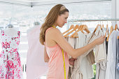 Beautiful female fashion designer looking at clothes on rack in the store