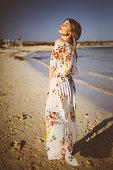 Beautiful young female tourist in swimwear enjoying the sun and relaxing at seaside