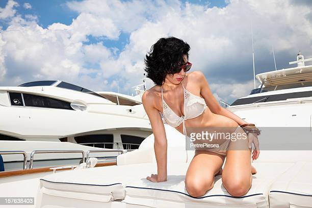 Beautiful fashion model sunbathing and posing on luxury yacht