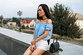 Beautiful fashionable asian woman in a blue blouse and white shorts with a bag sits on a background of the city.
