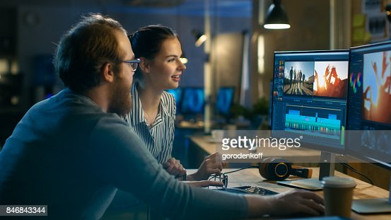 Beautiful Female and Handsome Male Video Editors Discuss Footage They're Working On. They Enjoy Working Together in a Cozy Creative Studio. : Stock Photo