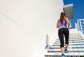 Beautiful female athlete running up the stairs