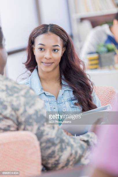 Beautiful female college student talks with army recruiter
